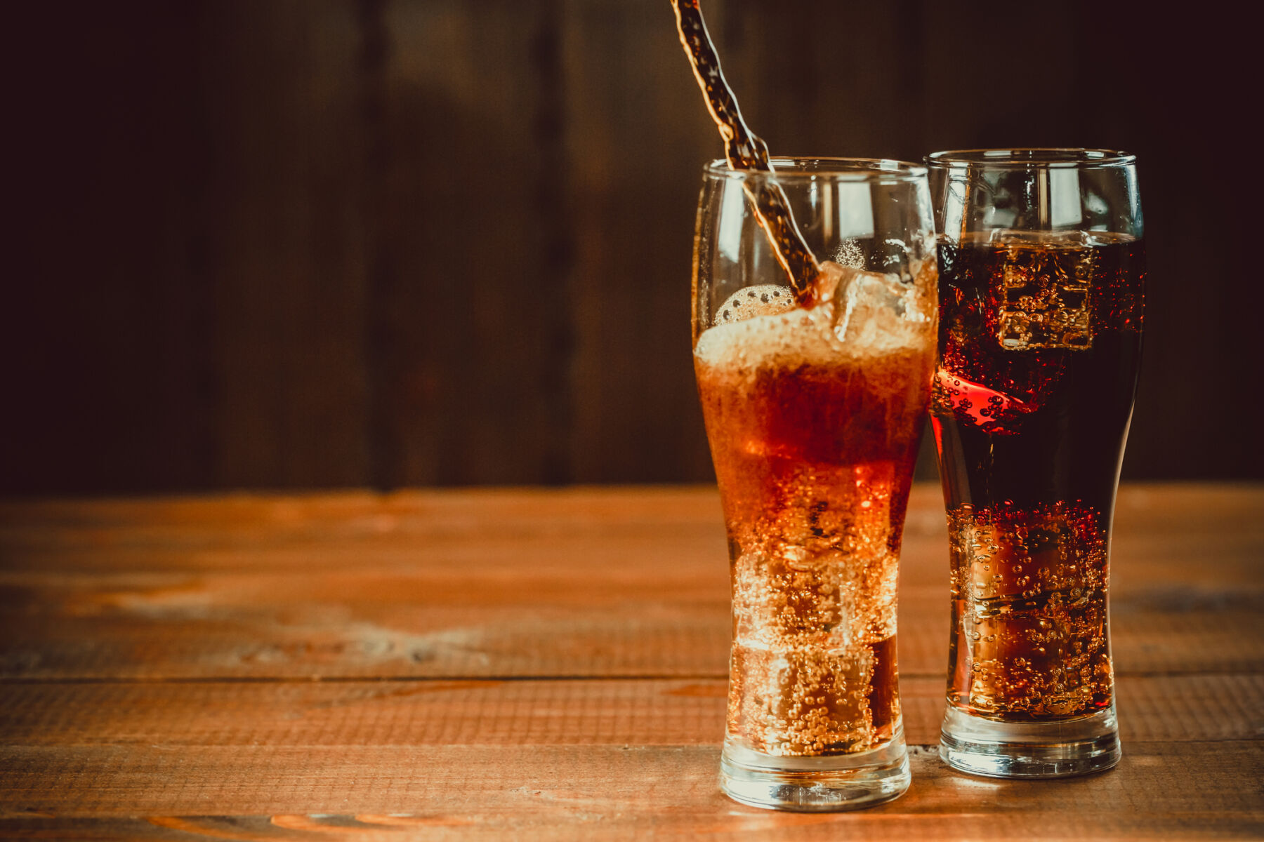 Pouring beautiful cold drink of Cola with ice cubes with a boiler straws in glasses on wooden background with free space. Shallow DOF.